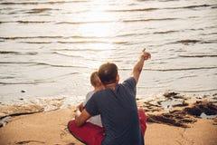 Ευτυχία τρόπου ζωής μπαμπάδων γιων και πατέρων αγοράκι που δείχνει την παραλία θάλασσας στοκ φωτογραφίες