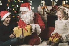 Ευτυχείς Άγιος Βασίλης και παιδιά γύρω από το διακοσμημένο χριστουγεννιάτικο δέντρο Στοκ εικόνα με δικαίωμα ελεύθερης χρήσης