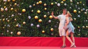Ευτυχείς άνδρας και γυναίκα ζευγών που κάνουν selfie στο τηλέφωνό τους στεμένος στα πλαίσια ενός χριστουγεννιάτικου δέντρου στο α απόθεμα βίντεο
