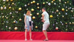 Ευτυχείς άνδρας και γυναίκα ζευγών που χορεύουν στο υπόβαθρο του χριστουγεννιάτικου δέντρου σε μια τροπική πόλη Η έννοια του νέου φιλμ μικρού μήκους