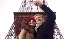 Ευτυχείς άνδρας και γυναίκα που χαμογελούν και που θέτουν για το selfie στο Παρίσι, μνήμες διακοπών Στοκ Φωτογραφία