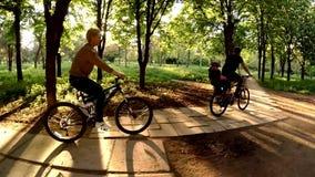 Ευτυχείς άνθρωποι που οδηγούν τα ποδήλατα στο πράσινο πάρκο φιλμ μικρού μήκους