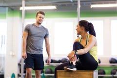 Ευτυχείς άνδρας και γυναίκα με τον ιχνηλάτη ποσοστού καρδιών στη γυμναστική Στοκ φωτογραφία με δικαίωμα ελεύθερης χρήσης