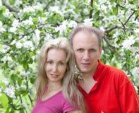 Ευτυχείς άνδρας και γυναίκα στα ανθίζοντας Apple-δέντρα Στοκ Φωτογραφίες