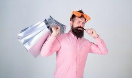 Ευτυχείς αγορές με τις τσάντες εγγράφου δεσμών Ψωνίζοντας εθισμένος καταναλωτής Γενειοφόρος δέσμη λαβής γυαλιών ηλίου ένδυσης hip στοκ εικόνα