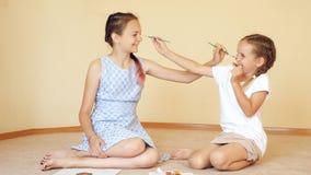Ευτυχείς αδελφές που παίζουν με τα πινέλα στοκ φωτογραφία