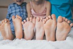 Ευτυχείς αδελφός και αδελφές που κάθονται στο κρεβάτι χωρίς παπούτσια Στοκ Εικόνες