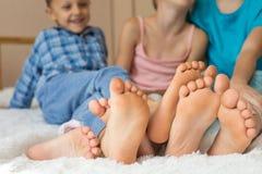 Ευτυχείς αδελφός και αδελφές που κάθονται στο κρεβάτι χωρίς παπούτσια Στοκ Φωτογραφία