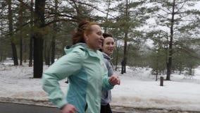 Ευτυχείς ανώτερες και νέες καυκάσιες γυναίκες που τρέχουν στο χιονώδες πάρκο το χειμώνα που μιλά και που χαμογελά o απόθεμα βίντεο