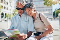 Ευτυχείς ανώτεροι τουρίστες που εξετάζουν έναν χάρτη πόλεων Στοκ Εικόνες