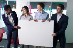 Ευτυχείς ανώτεροι υπάλληλοι που κρατούν ένα κενό έμβλημα στοκ φωτογραφία
