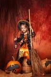 Ευτυχείς αποκριές! όμορφο μικρό κορίτσι στο κοστούμι μαγισσών με το MAG Στοκ Εικόνες