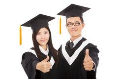Ευτυχείς απόφοιτοι φοιτητές ζευγών με τους αντίχειρες επάνω στοκ εικόνα με δικαίωμα ελεύθερης χρήσης