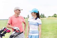 Ευτυχείς αρσενικοί και θηλυκοί παίκτες γκολφ που επικοινωνούν ενάντια στο σαφή ουρανό Στοκ Εικόνες