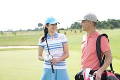 Ευτυχείς αρσενικοί και θηλυκοί παίκτες γκολφ που επικοινωνούν στη σειρά μαθημάτων Στοκ εικόνες με δικαίωμα ελεύθερης χρήσης