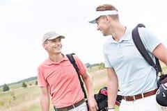 Ευτυχείς αρσενικοί παίκτες γκολφ που συζητούν ενάντια στο σαφή ουρανό Στοκ Εικόνες