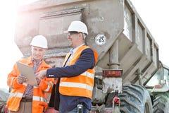 Ευτυχείς αρχιτέκτονες που συζητούν πέρα από την περιοχή αποκομμάτων από το φορτηγό κατασκευής Στοκ Εικόνες
