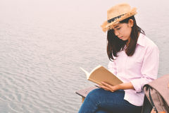 Ευτυχείς ασιατικές γυναίκες που διαβάζουν ένα βιβλίο και ένα σακίδιο πλάτης Στοκ Φωτογραφία