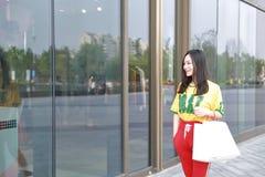 Ευτυχείς ασιατικές κινεζικές σύγχρονες μοντέρνες τσάντες αγορών γυναικών σε μια περιστασιακή κατανάλωση γέλιου χαμόγελου αγοραστώ στοκ φωτογραφία