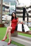 Ευτυχείς ασιατικές κινεζικές σύγχρονες μοντέρνες τσάντες καρτών αγορών ποδιών κοριτσιών γυναικών σε ένα περιστασιακό γέλιο χαμόγε στοκ εικόνα