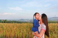 Ευτυχείς ασιατικές μητέρα και κόρες που φιλούν στον τομέα λιβαδιών στο πρωί στοκ φωτογραφίες