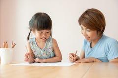 Ευτυχείς ασιατικές μητέρα και κόρη που σύρουν από κοινού στοκ εικόνα