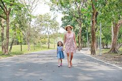 Ευτυχείς ασιατικές mom και κόρη που περπατούν στην οδό στο θερινό πάρκο στοκ εικόνα