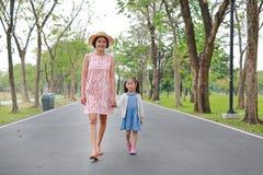 Ευτυχείς ασιατικές mom και κόρη που περπατούν στην οδό στο θερινό πάρκο στοκ φωτογραφίες