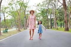 Ευτυχείς ασιατικές mom και κόρη που περπατούν στην οδό στο θερινό πάρκο στοκ φωτογραφία με δικαίωμα ελεύθερης χρήσης
