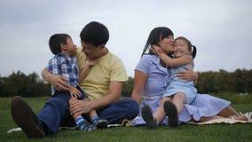 Ευτυχείς ασιατικοί γονείς που αγκαλιάζουν τα χαρούμενα παιδιά τους φιλμ μικρού μήκους