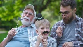 Ευτυχείς αστείοι οικογενειακοί γιος και μπαμπάς, granddad με το πλαστό mustache, καπέλο, eyeglasses στις διακοπές υπαίθριες στο π απόθεμα βίντεο