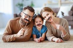 Ευτυχείς αστείοι πατέρας οικογενειακών μητέρων και κόρη παιδιών με το mustache στο ραβδί στοκ εικόνες