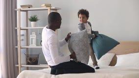 Ευτυχείς αφρικανικοί μπαμπάς και γιος που έχουν την πάλη μαξιλαριών στο κρεβάτι απόθεμα βίντεο