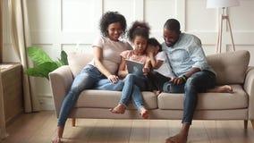 Ευτυχείς αφρικανικοί οικογενειακοί γονείς και μικρά παιδιά που χρησιμοποιούν την ψηφιακή ταμπλέτα φιλμ μικρού μήκους