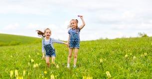 Ευτυχείς αδελφές διδύμων παιδιών που πηδούν και που γελούν το καλοκαίρι Στοκ εικόνες με δικαίωμα ελεύθερης χρήσης