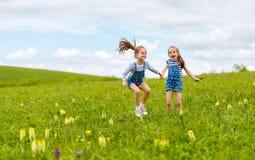 Ευτυχείς αδελφές διδύμων παιδιών που πηδούν και που γελούν το καλοκαίρι Στοκ εικόνα με δικαίωμα ελεύθερης χρήσης
