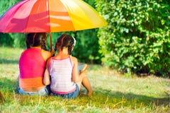 Ευτυχείς αδελφές κάτω από τη ζωηρόχρωμη ομπρέλα στο πάρκο Στοκ φωτογραφίες με δικαίωμα ελεύθερης χρήσης
