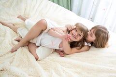 Ευτυχείς αδελφές μικρών κοριτσιών που αγκαλιάζουν και που φιλούν Στοκ Φωτογραφία