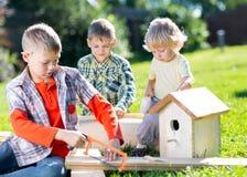 Ευτυχείς αδελφοί παιδιών που κάνουν το ξύλινο birdhouse με το χέρι Στοκ φωτογραφία με δικαίωμα ελεύθερης χρήσης