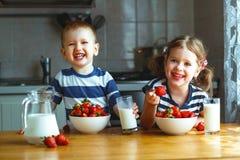 Ευτυχείς αδελφός και αδελφή παιδιών που τρώνε τις φράουλες με το γάλα Στοκ εικόνες με δικαίωμα ελεύθερης χρήσης