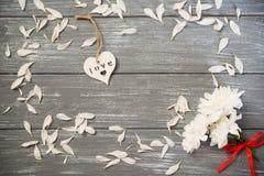ευτυχείς βαλεντίνοι ημέ&rho Διακοσμητική άσπρη ξύλινη καρδιά γκρίζο σε αγροτικό, whith λουλούδια, έννοια βαλεντίνων ` s στοκ φωτογραφία