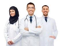 Ευτυχείς γιατροί στα άσπρα παλτά με τα στηθοσκόπια Στοκ Φωτογραφίες