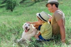 Ευτυχείς γονέας και γιος που κτυπούν το κατοικίδιο ζώο του Λαμπραντόρ Στοκ φωτογραφίες με δικαίωμα ελεύθερης χρήσης