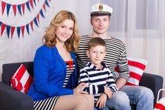 Ευτυχείς γονείς και λίγος γιος στην ομοιόμορφη συνεδρίαση ναυτικών στο ντεκόρ Στοκ Φωτογραφία