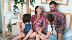 Ευτυχείς γονείς και δύο κόρες έχουν τον καλό χρόνο μαζί στο σπίτι, κάθονται στο κρεβάτι απόθεμα βίντεο