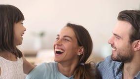 Ευτυχείς γονείς και κόρη παιδιών που αγκαλιάζει την εξέταση γέλιου τη κάμερα απόθεμα βίντεο