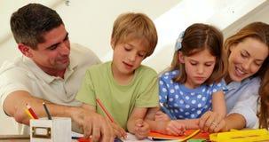 Ευτυχείς γονείς και παιδιά που σύρουν από κοινού φιλμ μικρού μήκους