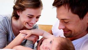 Ευτυχείς γονείς που εναπόκεινται στο χαριτωμένο γιο μωρών τους στο κρεβάτι απόθεμα βίντεο