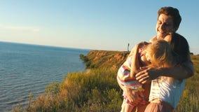 Ευτυχείς γονείς που κρατούν την κόρη της στα όπλα και το φιλί της φιλμ μικρού μήκους
