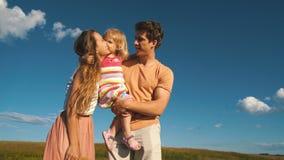 Ευτυχείς γονείς που κρατούν την κόρη της στα όπλα και το φιλί της απόθεμα βίντεο